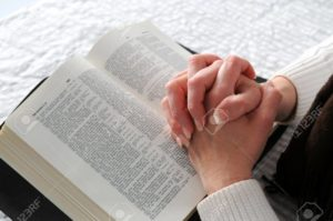 7752227 Woman S Hands Clasped In Prayer Over An Open Bible